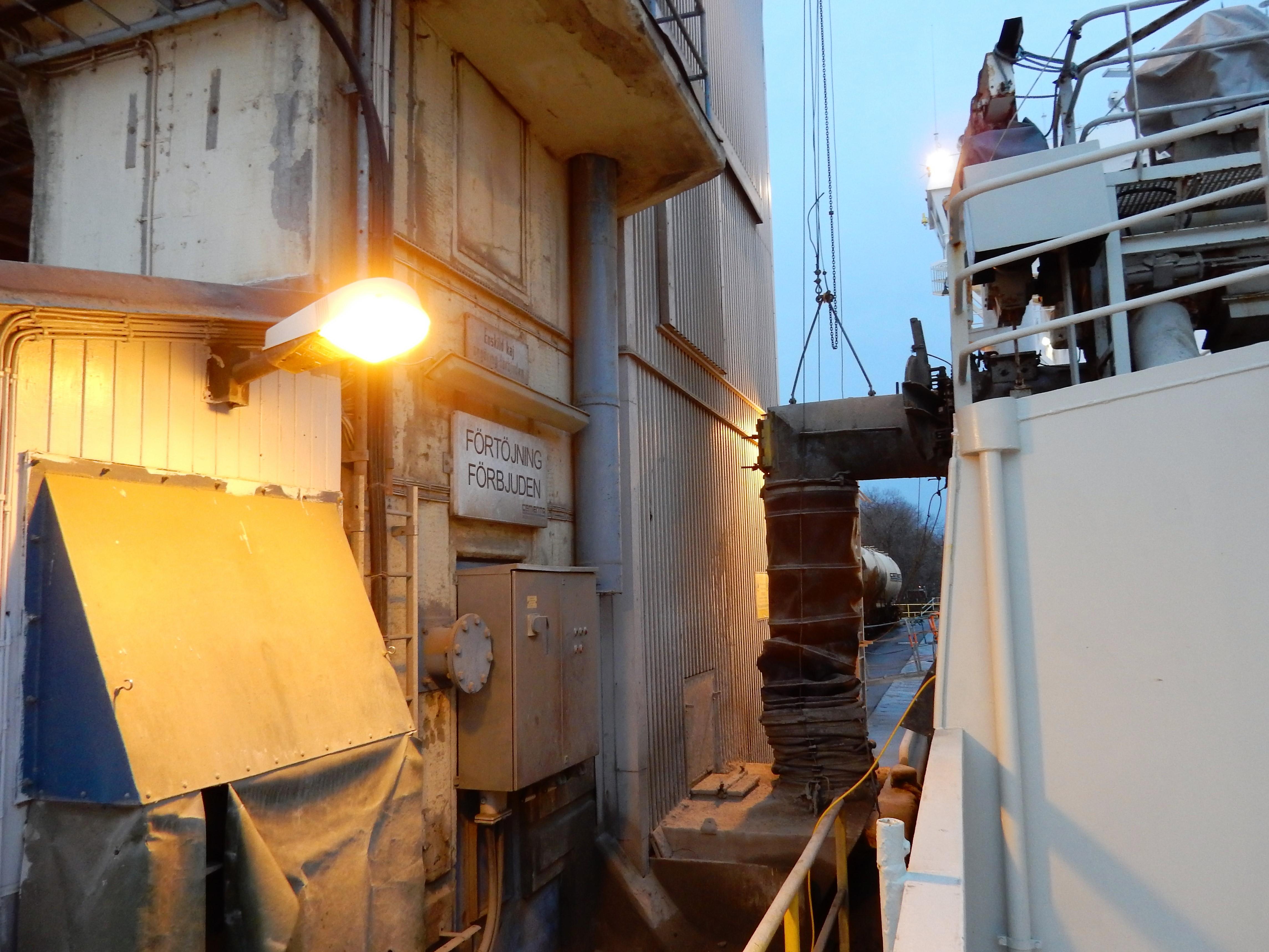 Cementen förs över från båten till depån i en så kallad strumpa.